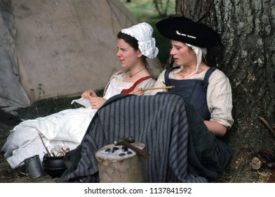 Battle Abbey Sussex UK 1996. Two unidentified female reenactors wear period 18th Century clothing they sit against a tree at a re-enactment of the American Indian Wars.