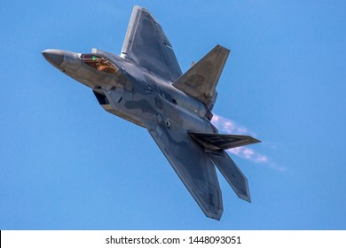 BATTLE CREEK, MICHIGAN / USA - July 7, 2019: A United States Air Force F-22 Raptor performs flybys during sunset at the 2019 Battle Creek Field of Flight Airshow.