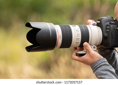 Battle Ground, WA / USA - August 25 2018: Male person holding Canon 5D Mark IV DSLR with 70-200mm f2.8 lens.