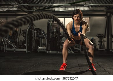 Battle ropes session. Attractive young fit and toned sportswoman working out in functional training gym doing crossfit exercise with battle ropes copyspace battling ropes cross-fit workout motivation