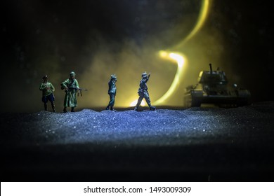 Battle scene. Military silhouettes fighting scene on war fog sky background. A German soldiers raised arms to surrender. Plastic toy soldiers with guns taking prisoner the enemy soldier. Artwork