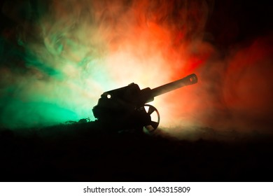 Battle scene. Silhouette of old field gun standing at field ready to fire. With colorful dark foggy background. Selective focus