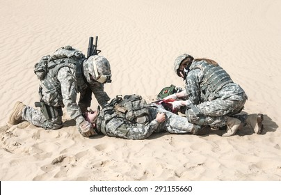 Battlefield medic saving life of injured airborne infantry paratrooper on desert sand. Wounded warrior screaming pain suffering but he will be alive