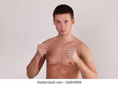battler man ready to fight. studio shoot on gray background
