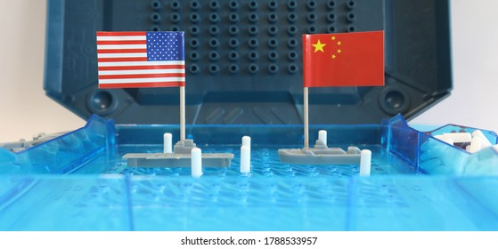 A battleship game board featuring a US navy warship and a Chinese naval ship with national flags. South China sea news and international waters navigation conflict confrontation concept