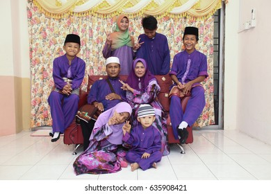 Batu Pahat, Malaysia - August 8, 2013:  Muslim family in traditional Malay clothing during Eidul Fitri celebration at  Batu Pahat , Malaysia. Family, forgiveness and Happiness Concept.