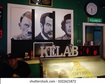 Batu Pahat, Malaysia - February 11, 2018 : A posters of Adolf Hitler, Saddam Hussein, and Muammar Gaddafi on green wall under low light restaurant in Johor.