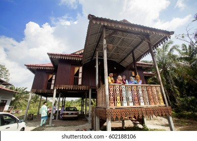 Batu Pahat, Malaysia -July 17, 2015 :  Happy Malay family in traditional clothing and traditional malay house during Hari Raya. Malaysian family lifestyle at home. Happiness concept.