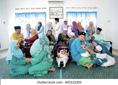 Batu Pahat, Malaysia - July 17 , 2015:  Muslim family in traditional Malay clothing during Eidul Fitri celebration at  Batu Pahat , Malaysia. Family and Happiness Concept.