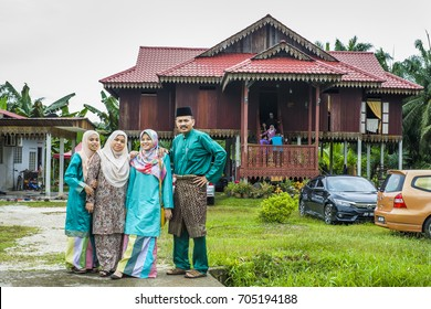Batu Pahat, Malaysia-June 26 , 2017: Happy  family posing for the camera togather in front traditional Malay house during Eidul Fitri celebration at Batu Pahat , Malaysia. Family and Happiness Concept
