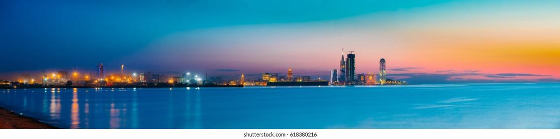 Batumi, Adjara, Georgia - May 25, 2016: Panorama of illuminated resort town at sunset. Port, Radisson Blu Hotel, Black Sea Technological University, Porta Batumi Tower, ferris wheel and Alphabet Tower