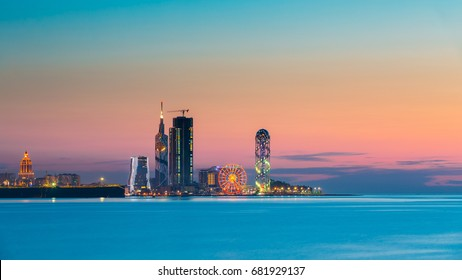 Batumi, Adjara, Georgia - May 25, 2016: Panorama of illuminated resort town at sunset. Radisson Blu Hotel, Black Sea Technological University, Porta Batumi Tower, ferris wheel and Alphabet Tower
