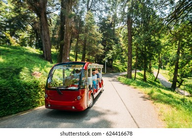Batumi, Adjara, Georgia - May 27, 2016: Tourist Waving His Hand From A Red Passing Electric Car For Exploring And Sightseeing Of The Botanical Garden. Tour In Sunny Summer Day