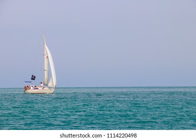 Batumi, Adjara, Georgia - May 3, 2018: Sailboat with white sails sailing in Black sea near coast of Batumi, Georgia