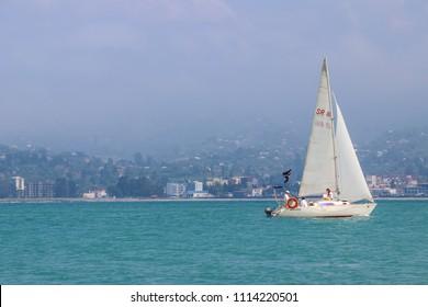 Batumi, Adjara, Georgia - May 3, 2018: Sailboat with white sails sailing in Black sea near coast of Batumi, Georgia