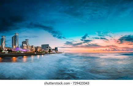 Batumi, Adjara, Georgia. Panorama Of Illuminated Resort Town At Sunset. Modern Multi-storey Residential Buildings And Hotels Near The Black Sea Coast In Night Illuminations Lights.