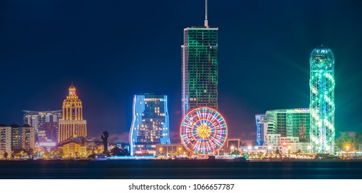 Batumi, Adjara, Georgia. Panorama Of Modern Architecture In Seafront. Miracle Park In Night Or Evening Illuminations Lights, Illuminated Resort Town Cityscape With Skyscrapers And Alphabet Tower