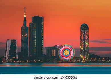 Batumi, Adjara, Georgia. Scene Of Resort Town At Sunset Or Sunrise. Bright Evening Sky. View From Sea Beach To Illuminated Cityscape With Urban Architecture, Skyscrapers And Tower. Golden Hour