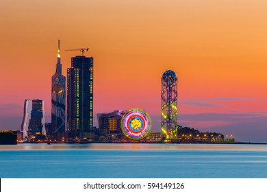 Batumi, Adjara, Georgia. Scene Of Resort Town At Sunset Or Sunrise. Bright Evening Sky. View From Sea Beach To Illuminated Cityscape With Modern Urban Architecture, Skyscrapers And Tower. Golden Hour