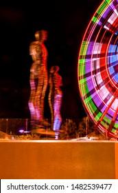 "Batumi, Adjara/Georgia - August 05 2019: Ferris wheel and a moving metal sculpture ""Ali and Nino"" at night."