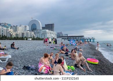 Batumi, Adjaria, Georgia - June 12 2018: Batumi city stone beach with Russian and European tourists having rest, swimming and watching sunset.