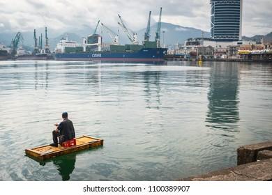 Batumi, Adjaria, Georgia - May 22 2018: fisherman fishing on his handmade boat in waters of Black Sea in Batumi city harbor and bay. View at cargo marine station with cranes and ships.
