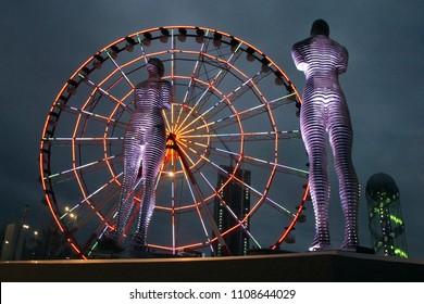 Batumi, Georgia - 07.09.2016: Ferris wheel and a moving metal sculpture created by Georgian sculptor Tamara Kvesitadze in 2007, titled Man and Woman or Ali and Nino.