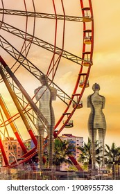 Batumi. Georgia -  08 September, 2018: Moving metal sculpture Ali and Nino and Ferris wheel.