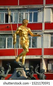 BATUMI, GEORGIA 09 19 2019: Golden statue of Neptune in front of Batumi Drama Theater in Batumi is an impressive landmark in Europe Square.