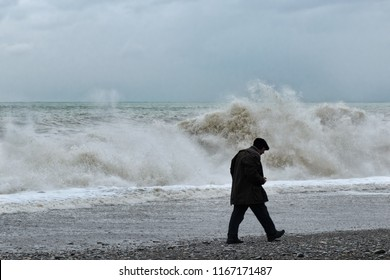 Batumi, Georgia, 2017-10-31: Dramatic, stormy weather at sea, single, lonely old man walking along coast, back view. Big waves as a symbol of life's difficulties, violent emotion, anxiety.