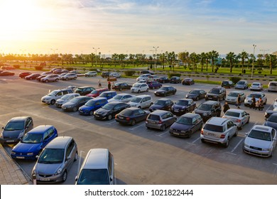 Batumi, Georgia, 2017-12-03: A lot of cars at open parking, people walk, in the background of palm trees, green trees and the sun shines. Top view. Empty space for text.