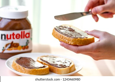 Batumi, Georgia - 24 November, 2018. Spread nutella pieces on a long loaf. Sandwiches with nut, chocolate, sweet paste and milk for a breakfast. Nutella breakfast