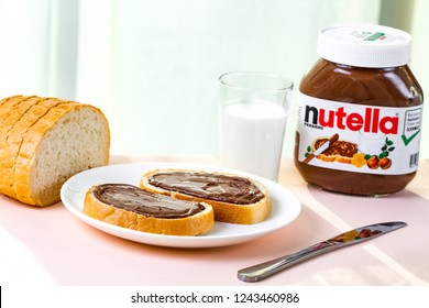 Batumi, Georgia - 24 November, 2018. Spread nutella on freshly baked bread. Sandwiches with nut, chocolate, sweet paste and milk for a breakfast. Nutella breakfast