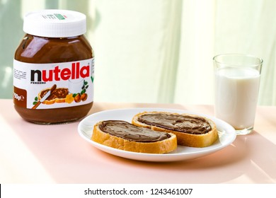 Batumi, Georgia - 24 November, 2018. Spread nutella pieces on a long loaf. Nut chocolate cream sandwich and milk for a breakfast. Nutella breakfast
