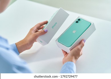 Batumi, Georgia. 27 July 2020 - Unpacking box of mint green iPhone 11 with dual camera of 2019 release. Apple gadgets