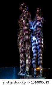 """Batumi, Georgia - August 28 2019: Night view to the moving metal love monument """"Ali&Nino"""" in Batumi. Figures are moving towards each other merging into a single entity, without touching."""