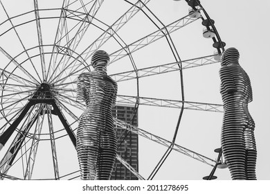 BATUMI, GEORGIA - JULY 2, 2021: Ali and Nino statue and The Ferris wheel in Batumi, Adjara, Georgia. Moving towards each other famous sculptures of Man and Woman in love. Black and white.