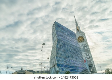 Batumi, Georgia - July 3 2019: Modern building of a skyscraper with a small ferris wheel and Radisson Blu Hotel against the sky with clouds on a summer day, photo from bottom to top