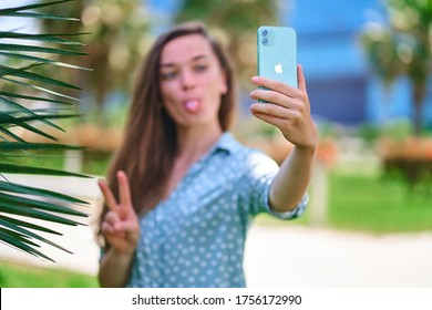 Batumi, Georgia - June 9, 2020. Modern fun woman stick out tongue and takes selfie photo on Iphone 11 green mint color outdoors