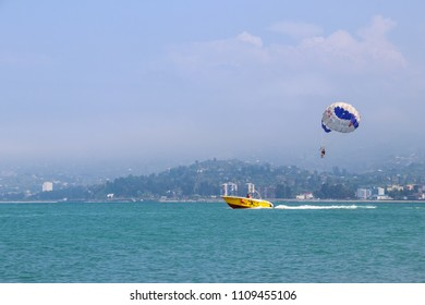 Batumi, Georgia - May 3, 2018: Parasailing on a calm blue sea with yellow motorboat towing a person suspended below a parachute by a harness