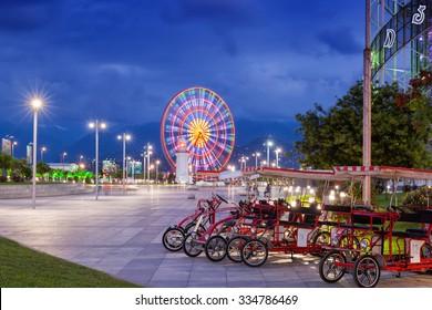 BATUMI, GEORGIA - September 18, 2015: Night view of Batumi - capital of Adjara, Georgia. Ferris wheel and bikes on seaside boulevard.