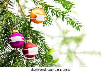 Baubles wearing face mask on fir branch, christmas and corona virus, covid-19 pandemic