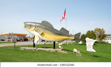 Baudette, Minnesota / USA - September 14 2018: Willie the Walleye sculpture, US flag, and plaque, proclaiming the city as walleye capital of the world