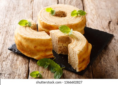 Baumkuchen, translated as tree cake, is a many-layered sponge cake baked on a rotating cylinder close-up on the table. horizontal