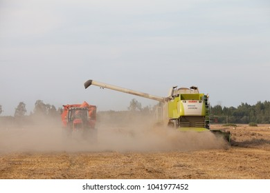 Bauska, Latvia - 2016/21/08: Class combine unloading wheat into a tractor trailer on a field in Bauska, Latvia