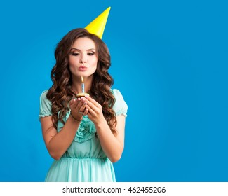 bautiful caucasian girl blowing candles on her cake.