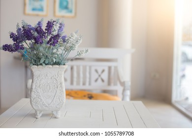 Bautiful purple flower in vintage flower pot on white table with sun lighting from window