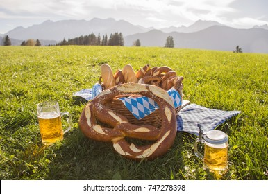 Bavaria bretzel with beer. Basket with Pretzels, beer mug in beautiful landscape from Bavaria, Allgau, Germany. Traditional pretzel and beer from Bavaria