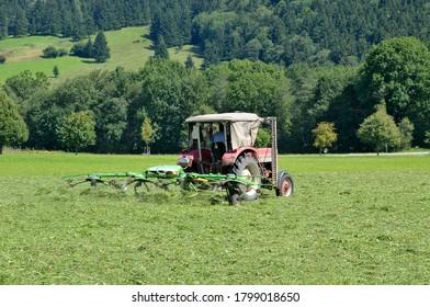 Bavaria, Germany - August 16, 2011: Farm tractor plowing farmland around Fussen