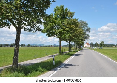 Bavaria, Germany - August 16, 2011: Country road in Schwangau with the church of St. Coloman in the background of the scana, a sunny day